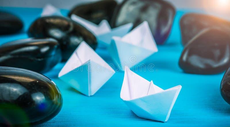 Bateaux d'avance de bateau de livre blanc de direction d'autres entre les pierres abstraites de roche sur le fond bleu La lumière photo stock