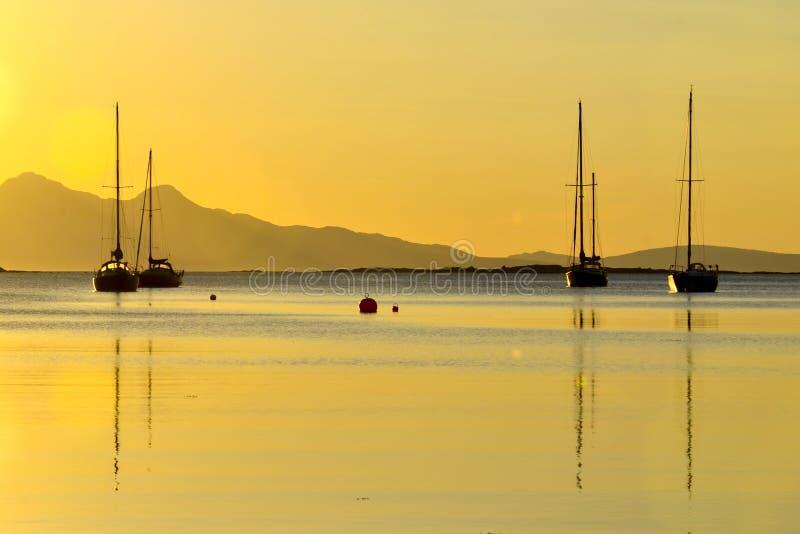Bateaux dans un coucher du soleil côtier d'or, Arisaig photographie stock libre de droits