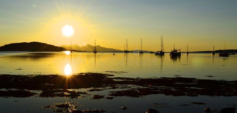 Bateaux dans un coucher du soleil côtier d'or, Arisaig image stock