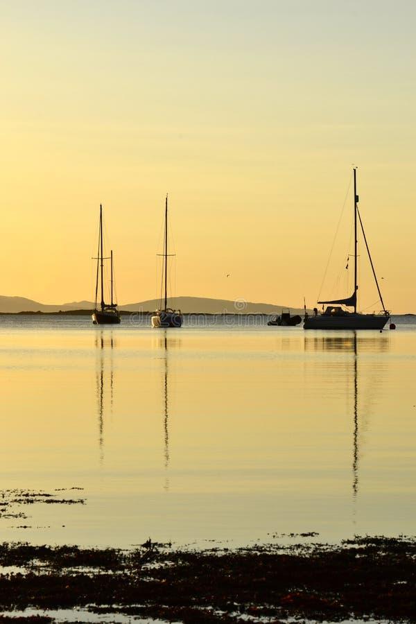 Bateaux dans un coucher du soleil côtier d'or, Arisaig images libres de droits