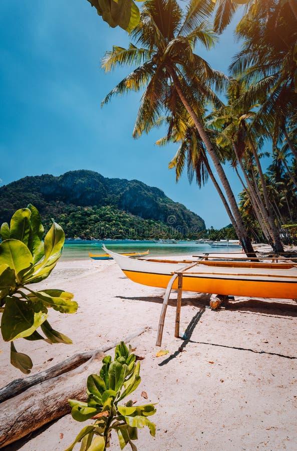 Bateaux de Banca sous des palmiers sur la plage sablonneuse dans le corong de Corong, EL Nido, Palawan, Philippines images libres de droits