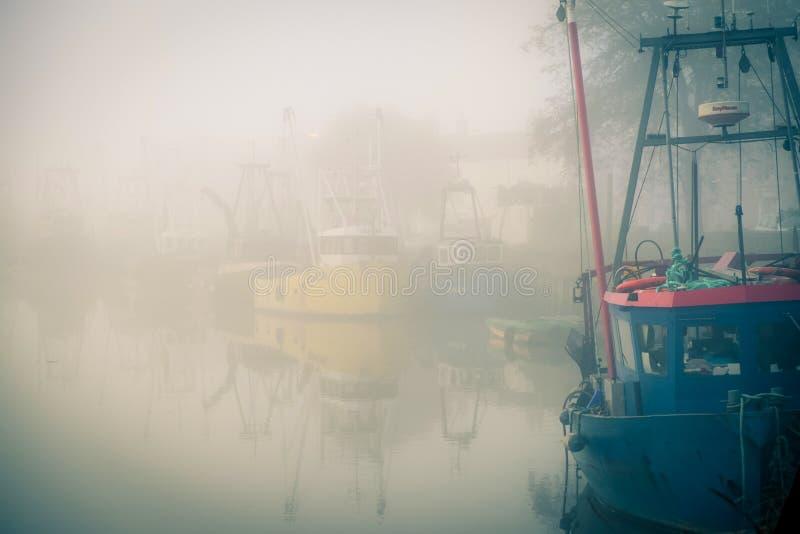 Bateaux de pêche amarrés sur une rivière brumeuse photo libre de droits