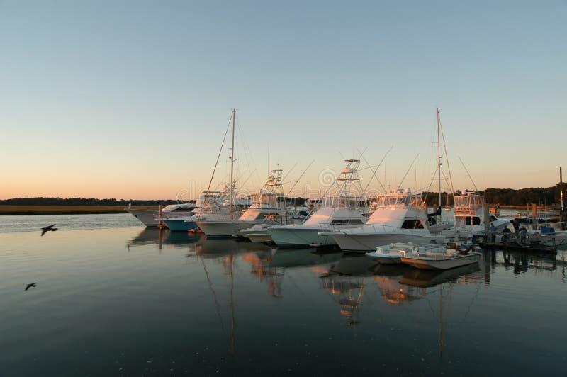 Bateaux de pêche au dock au coucher du soleil avec le vol de mouette près photos stock