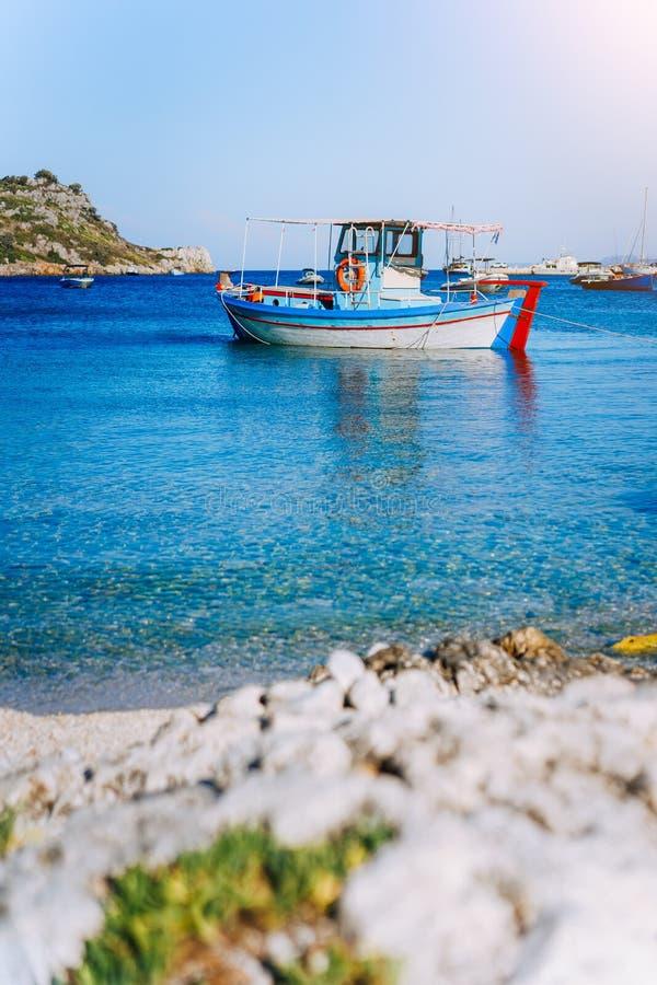 Bateaux de pêche grecs colorés à l'eau claire calme le matin de début de l'été photographie stock libre de droits