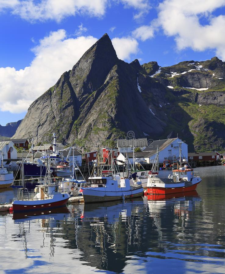 Bateaux de pêche norvégiens traditionnels en île de Lofoten, région de Reine avec des réflexions gentilles dans l'océan photo libre de droits