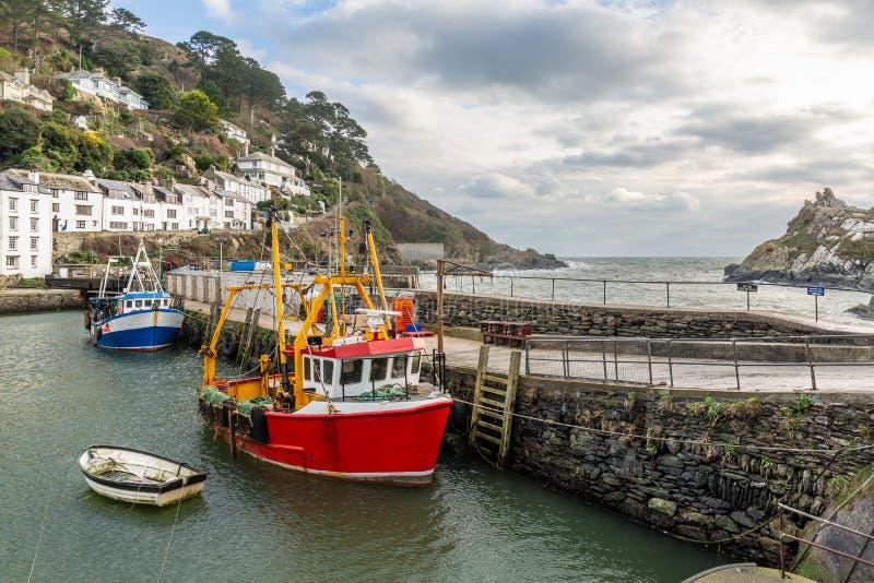 Bateaux de pêche rouges et bleus amarrés au port de Polperro, les Cornouailles, R-U photographie stock