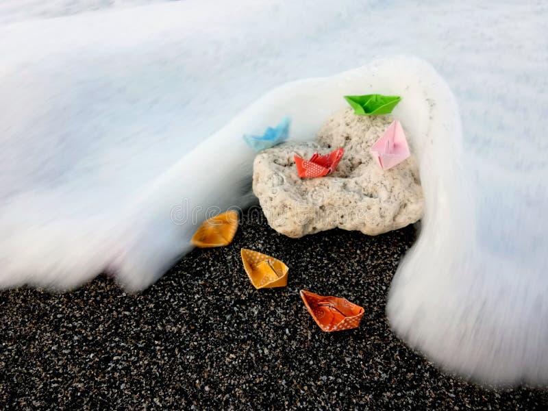 Bateaux de papier sur une roche photographie stock
