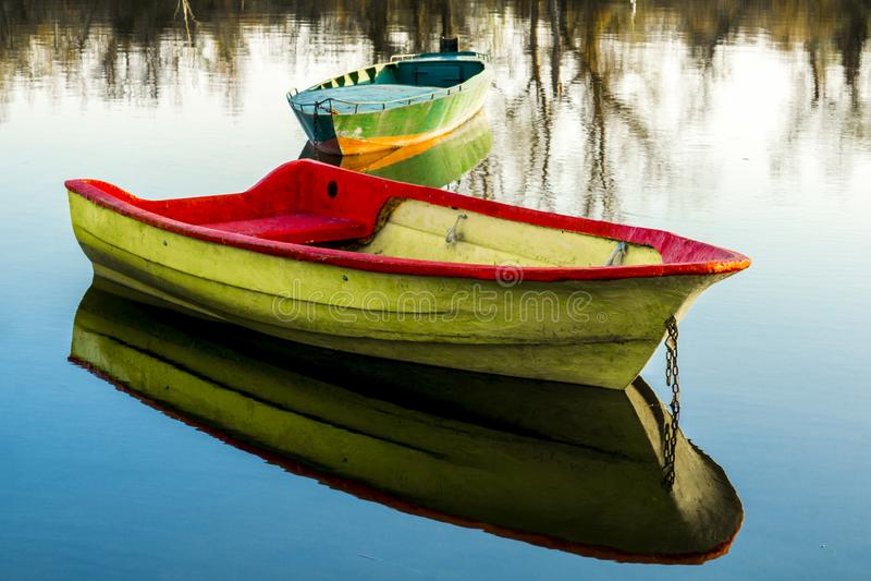 Bateaux en bois dans les eaux calmes du lac par jour de printemps image libre de droits