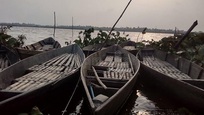 3 bateaux entrent sur la banque de la rivière dans le temps de coucher du soleil photographie stock