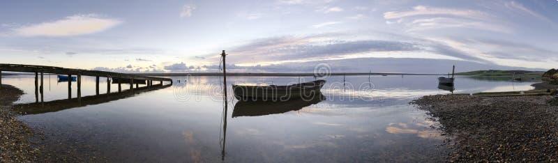 Bateaux et jetée au coucher du soleil images stock