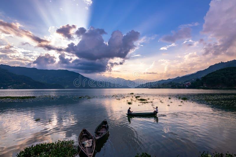 Bateaux naviguant pendant le cloudscape et le coucher du soleil oranges dramatiques dans le lac Phewa dans Pokhara, Népal image libre de droits