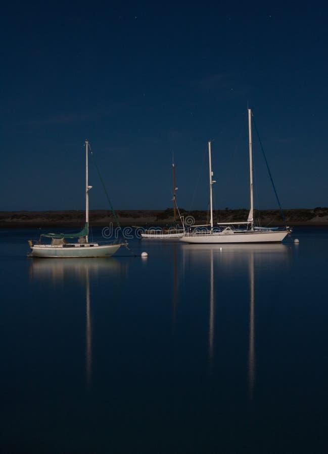 Bateaux réfléchissant la nuit éclairée par la lune dans la baie paisible photo libre de droits