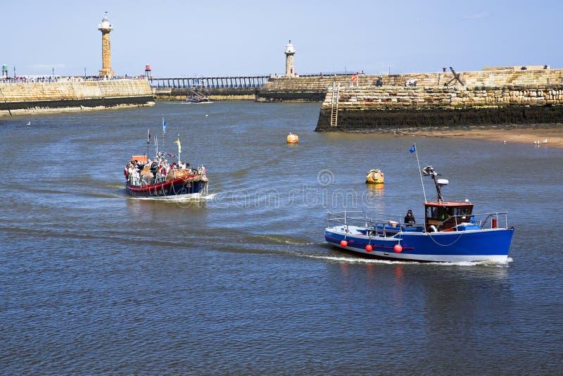 Bateaux retournant à Whitby Harbour images stock