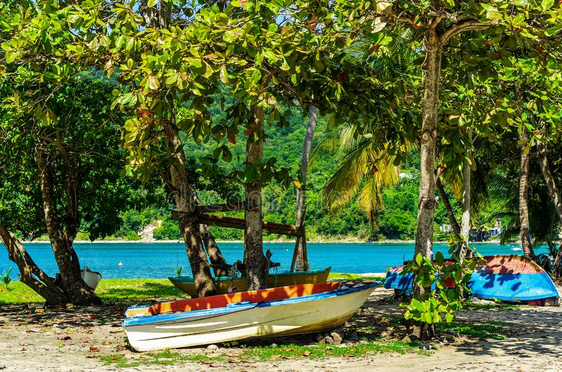 Bateaux se situant dans le sable sous des arbres à une plage sur la Guadeloupe photos libres de droits