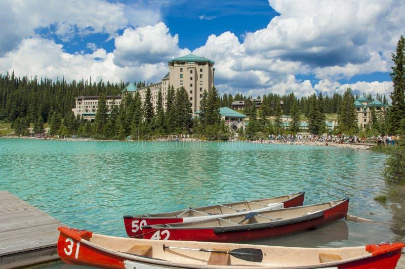 Bateaux sur la turquoise Lake Louise avec le château célèbre de Fairmont photographie stock