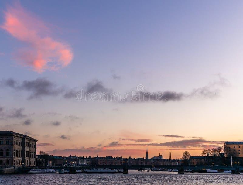 Bateaux, tours et ponts dans le port de Stockholm pendant un lever de soleil coloré en hiver - 2 photos stock