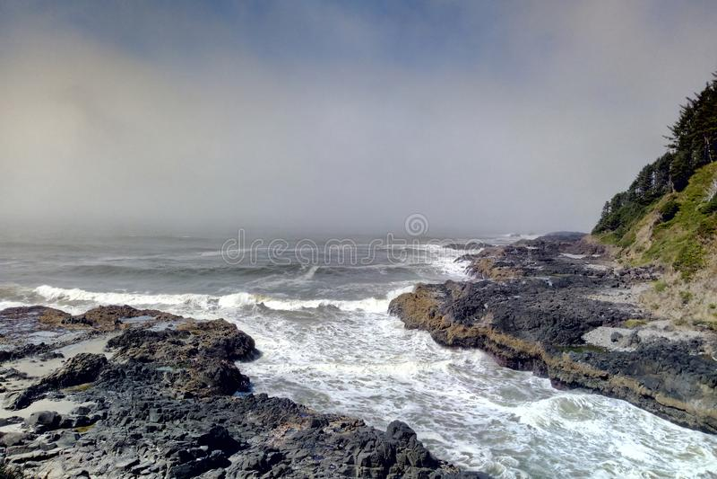 Batedeiras entrantes da maré da ressaca no canal estreito do poço do thor no cabo Perpetua, costa de Oregon imagem de stock