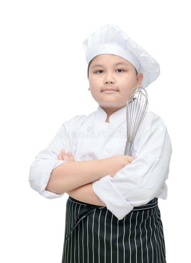Batedor de ovos da posse do cozinheiro chefe da criança com chapéu e avental do cozinheiro imagem de stock