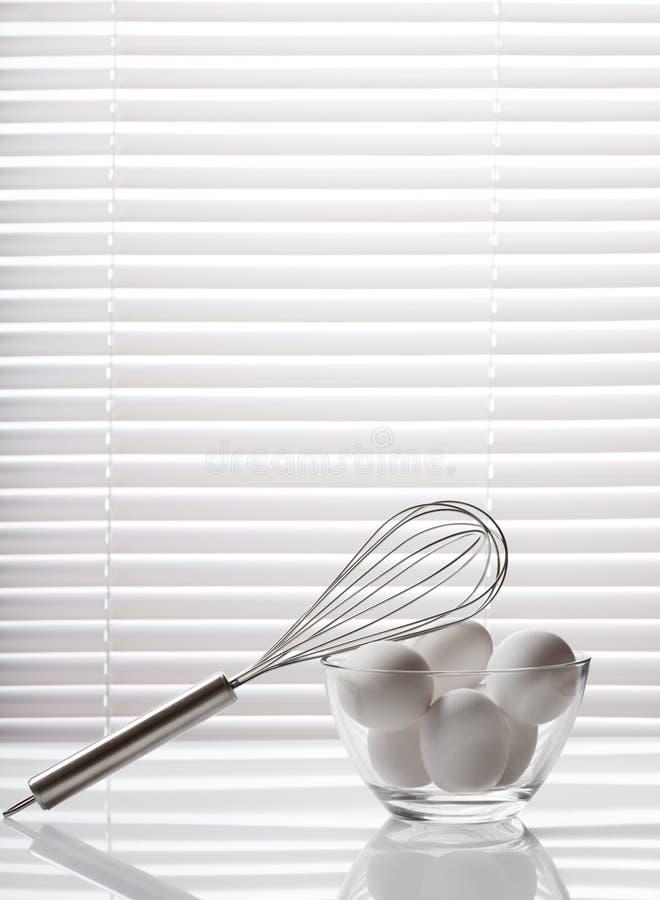 Batedor de ovos e bacia de vidro completamente de ovos imagem de stock
