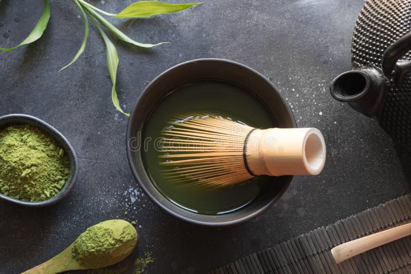 Batedor de ovos verde do chá do matcha da cerimônia e o de bambu na tabela preta Vista superior Espa?o para o texto foto de stock