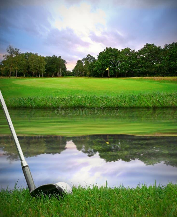 Batendo a esfera de golfe sobre o perigo da água foto de stock royalty free