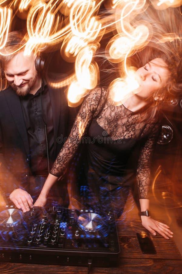 Batendo, partido, dança da menina com o DJ no console imagem de stock royalty free