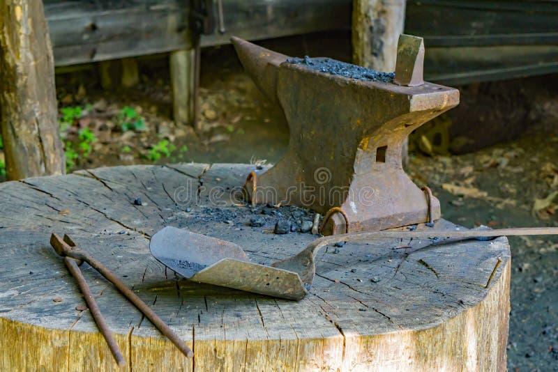 Batente, tenazes de brasa e pá de mão antigos em um ferreiro Shop fotografia de stock