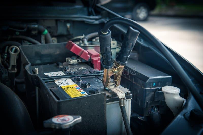 Batería de coche de carga con los cables de puente del canal de la electricidad foto de archivo