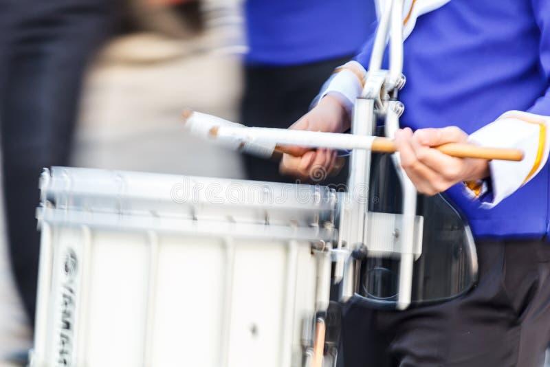 Batería de la trampa de la falta de definición de movimiento en el uniforme azul y blanco que juega el tambor en una marcha imagenes de archivo