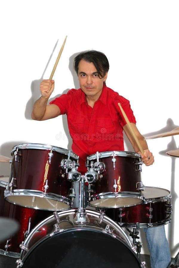 Batería en la camisa roja que juega los tambores aislados en un backg blanco fotografía de archivo libre de regalías