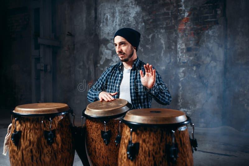 Batería que juega en los tambores de bongo de madera, ritmo del golpe fotografía de archivo