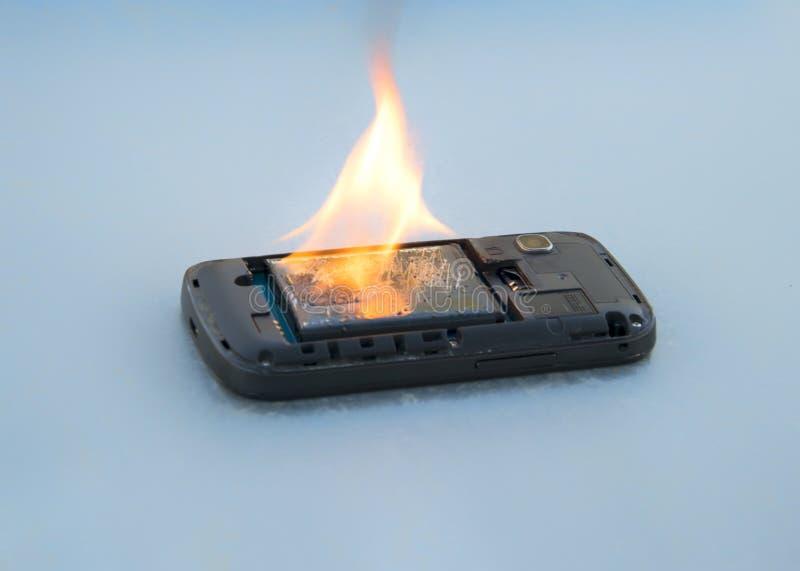 A bateria do telefone celular do conceito da segurança explode e as queimaduras devido ao superaquecimento fotos de stock