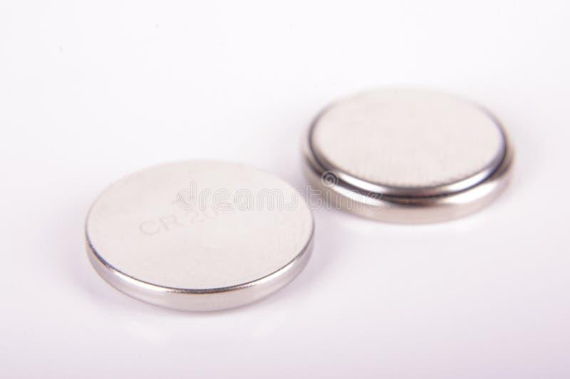 Baterias minúsculas da pilha do botão ambos os lados isolados imagem de stock