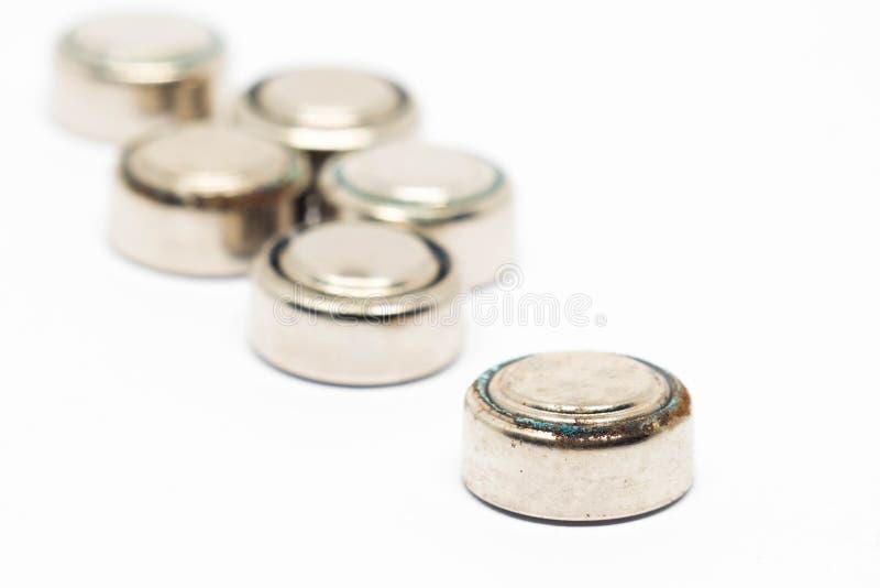 Baterias oxidadas do relógio pequeno isoladas no fundo branco foto de stock