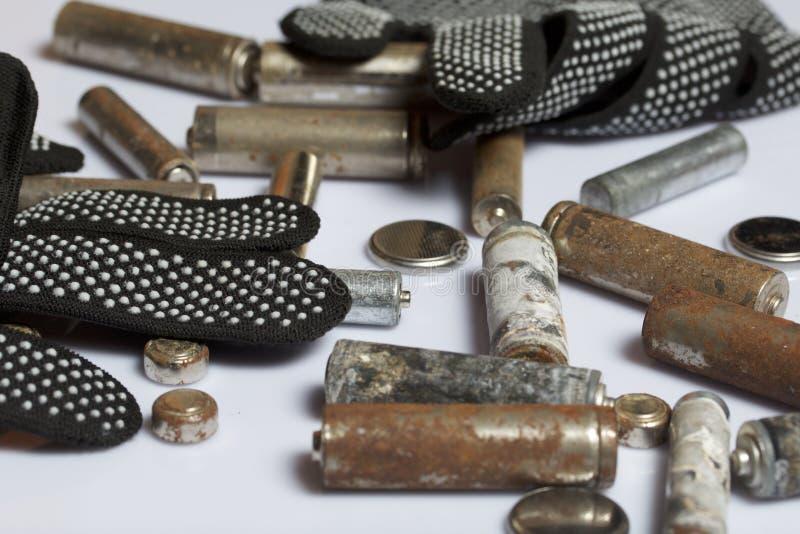 Baterias usadas da dedo-ferida cobertas com a corrosão Encontram-se em uma caixa de madeira Luvas de trabalho seguintes recycling imagens de stock