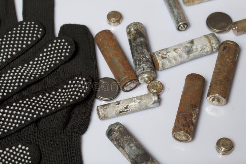 Baterias usadas da dedo-ferida cobertas com a corrosão Encontram-se em uma caixa de madeira Luvas de trabalho seguintes recycling foto de stock