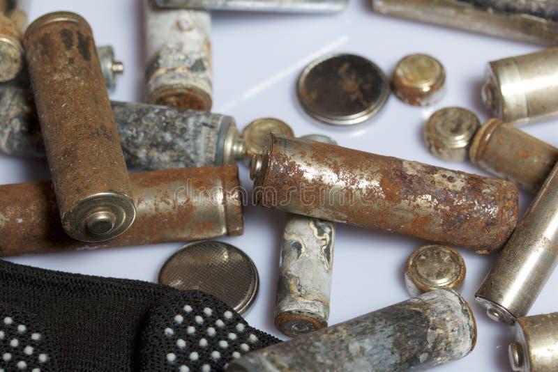 Baterias usadas da dedo-ferida cobertas com a corrosão Encontram-se em uma caixa de madeira Luvas de trabalho seguintes recycling fotografia de stock