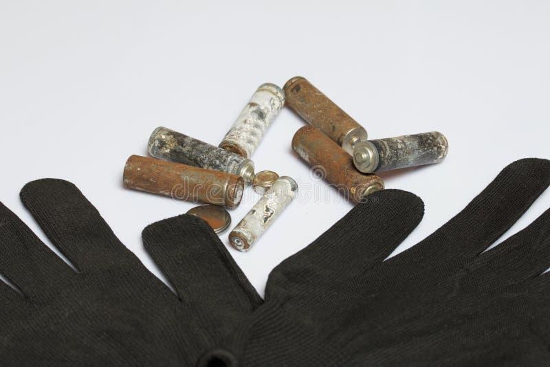 Baterias usadas da dedo-ferida cobertas com a corrosão Luvas de trabalho seguintes recycling imagem de stock royalty free