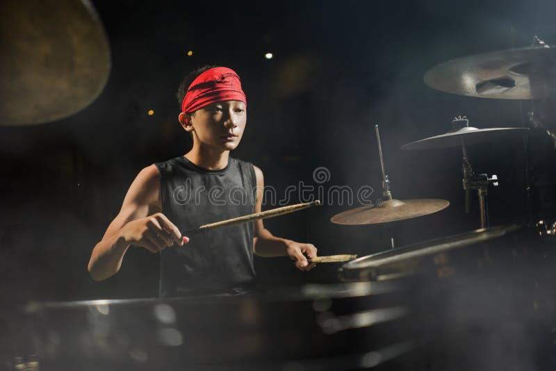 Baterista da banda de rock do Teenager Um jovem adolescente asiático-americano, fixe e talentoso, a tocar tambores em banda larga foto de stock