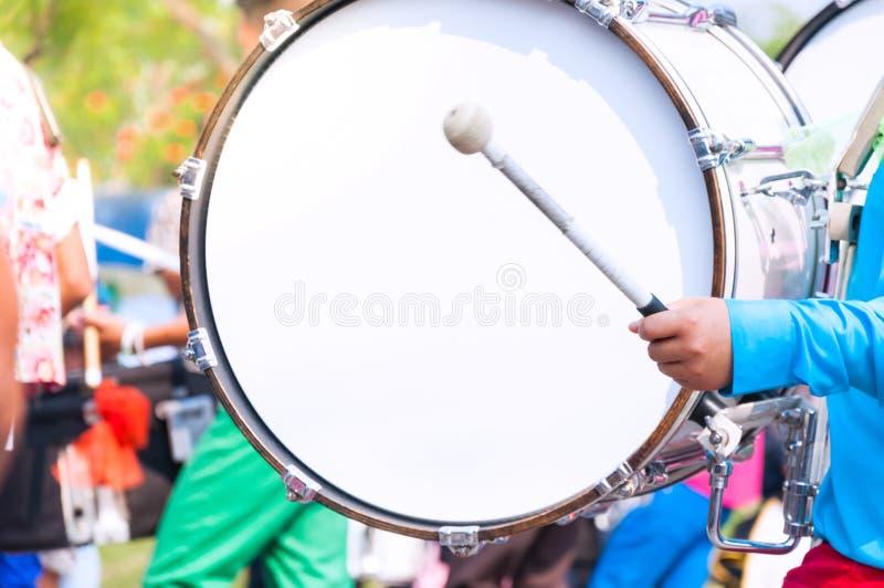 Baterista em uniformes azuis uma banda O baterista joga o cilindro grande na parada fotografia de stock