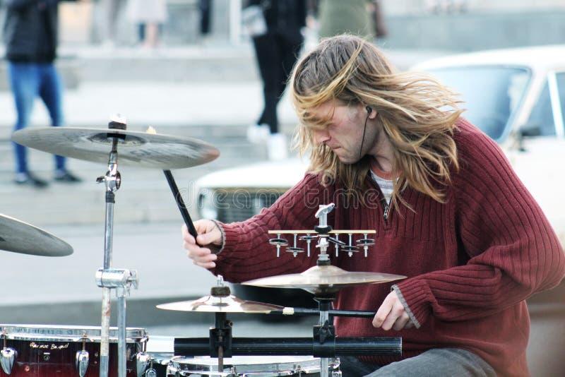 Baterista que joga cilindros no fundo blured da cidade Um homem que joga cilindros na rua Músico da rua que executa com o cilind imagem de stock