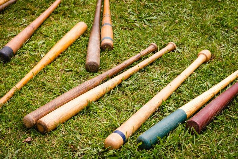 Bates de béisbol de la vendimia dispersados en la tierra imagen de archivo libre de regalías