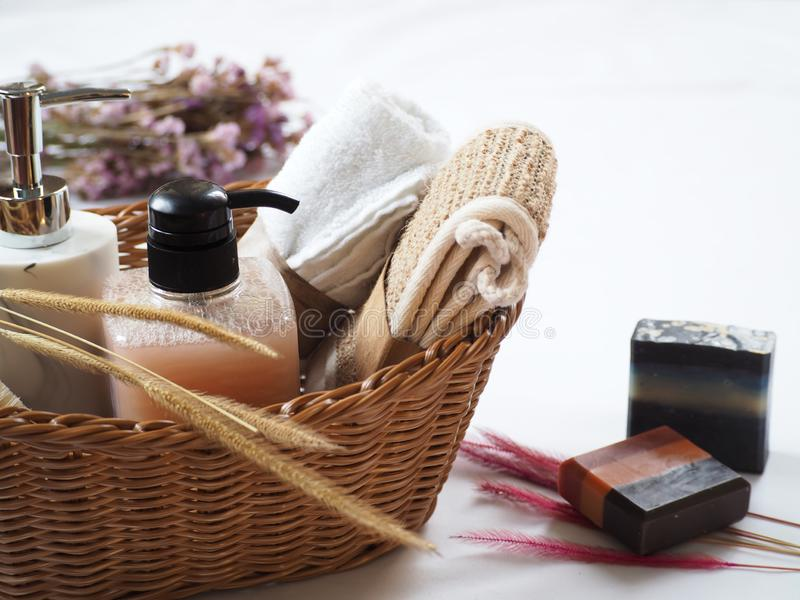 Bath accessories in the basket, natural homemade soap with flower decoration on white background royalty free stock image