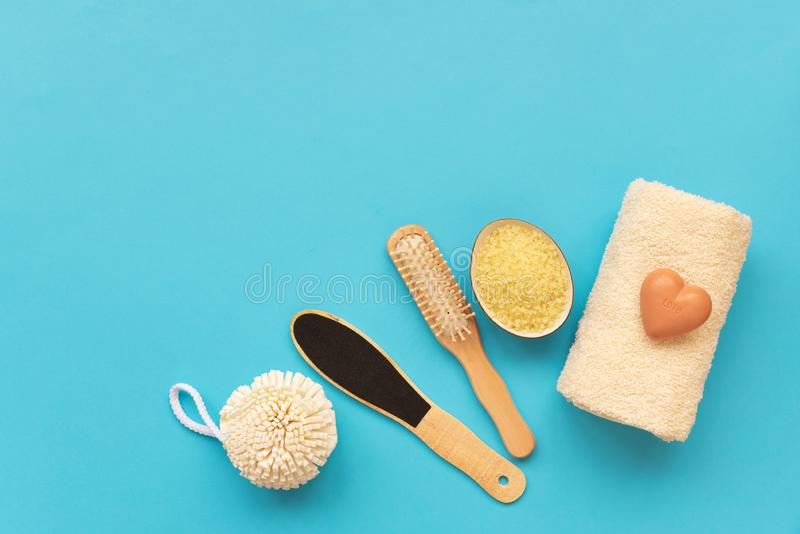 Bath accessories: towel, salt, brush, wisp, pumice and soap on blue background. Spa cosmetic or hygiene concept. Copy space. Flat. Lay. Top view. Flat lay stock photo