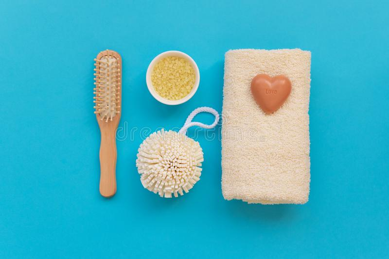 Bath accessories: towel, salt, brush, wisp, pumice and soap on blue background. Spa cosmetic or hygiene concept. Copy space. Flat. Lay. Top view. Flat lay stock photography