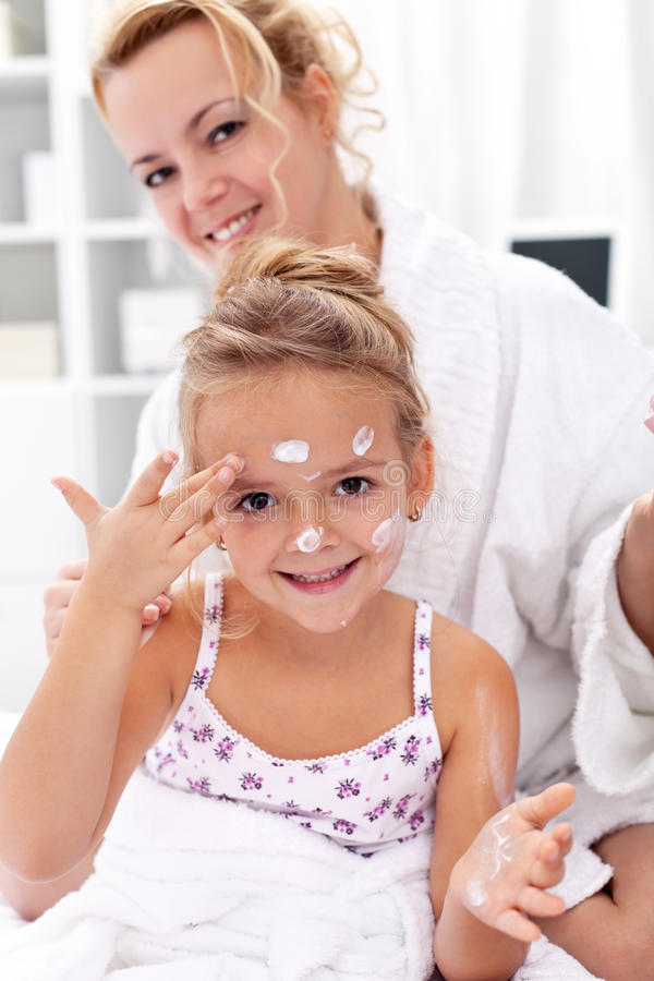 After bath body care - applying face cream. After bath body care with happy women and little girl stock image