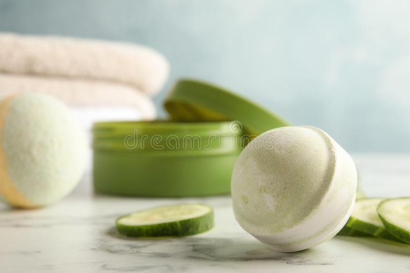 Bath bomb and cucumber slices on marble table royalty free stock photography