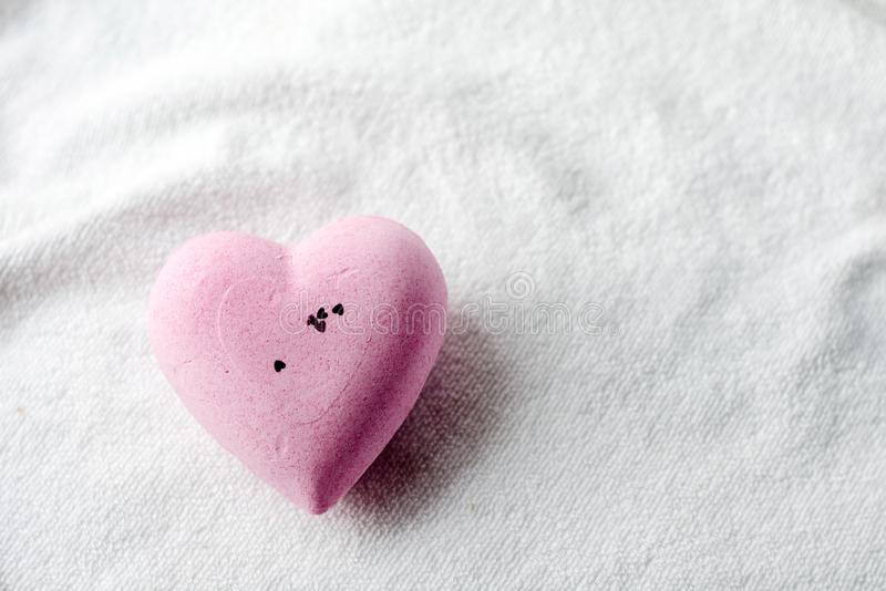 Bath bomb in the shape of a heart, lies on a white terry towel. Spa, aromatherapy and body skin care concept stock photos