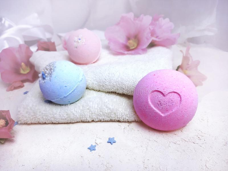 Bath bombs with towel   and flowers on white background. royalty free stock photo