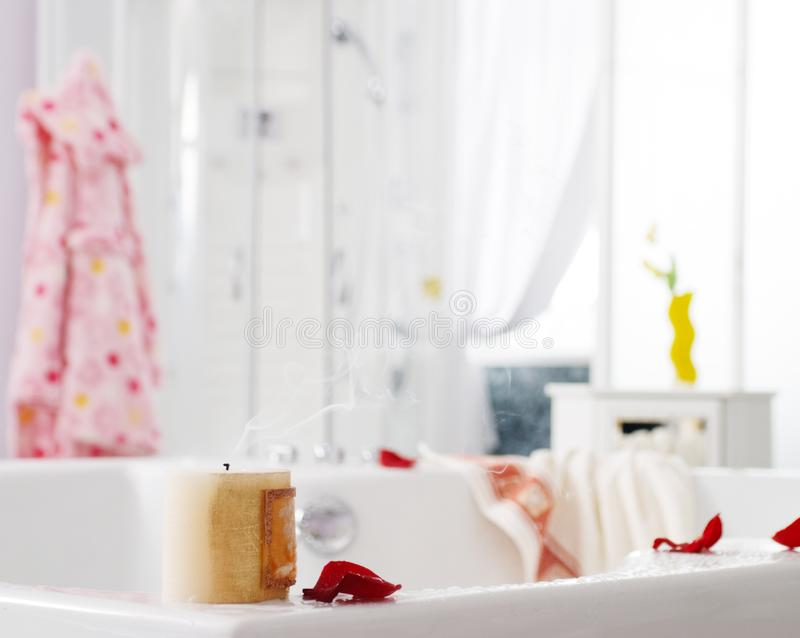 After bath - close up of bathroom interior with short focus on the rose petal and smoking candle stock photos